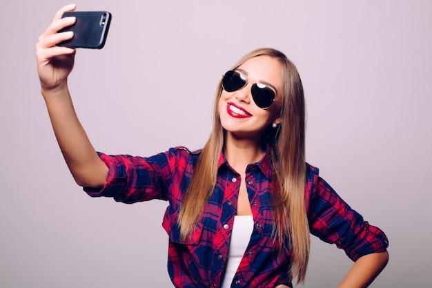 灰色の壁に隔離されたselfieを作る幸せなかわいい女性。 無料写真