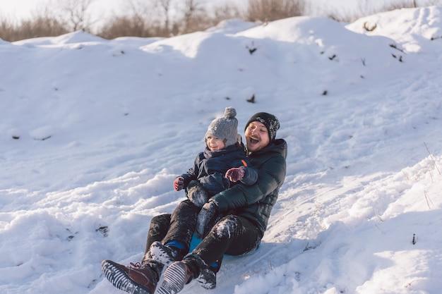 Счастливый папа и маленький мальчик играют со снежными санками Premium Фотографии