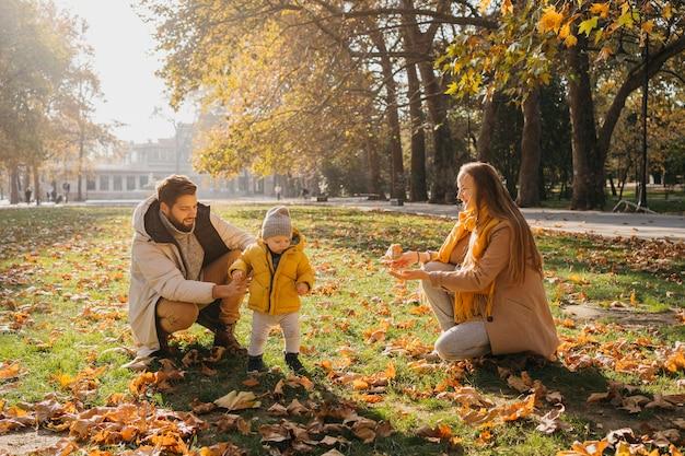 屋外で赤ちゃんと遊ぶ幸せなお父さんとお母さん 無料写真