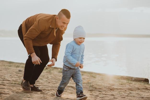 幸せなお父さんと息子は夏に川沿いのビーチの砂で遊ぶ Premium写真