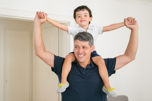Happy dad holding his son on shoulders and spreading hands. Free Photo