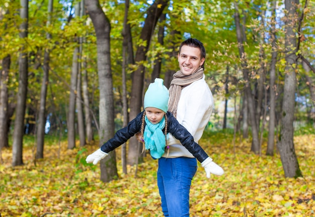 Happy dad and little daughter having fun in the park on sunny autumn day Premium Photo