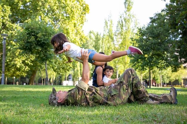 Papà felice sdraiato sull'erba e tenendo la figlia sulle mani dritte. padre caucasico che gioca con la ragazza carina. mamma e ragazzino seduto vicino a loro. ricongiungimento familiare, fine settimana e concetto di ritorno a casa Foto Gratuite