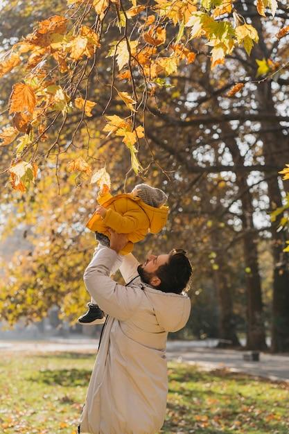 屋外で赤ちゃんと遊ぶ幸せなお父さん 無料写真