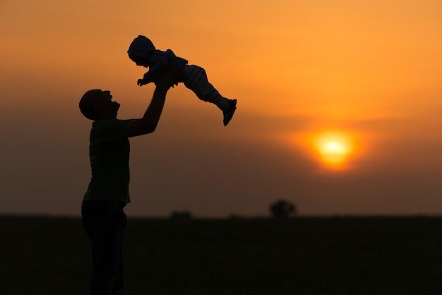 행복한 아빠는 일몰에 아기를 던졌습니다. 무료 사진