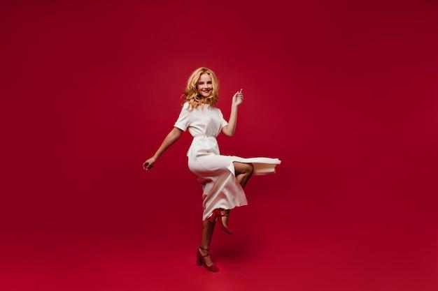 Счастливая танцевальная женщина улыбается на красной стене. очаровательная кудрявая девушка в длинном белом платье развлекается Бесплатные Фотографии