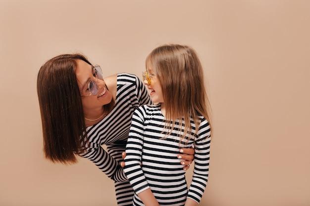 Felice donna dai capelli scuri con acconciatura corta guardando la sua affascinante ragazza sorridente e divertirsi su sfondo isolato Foto Gratuite