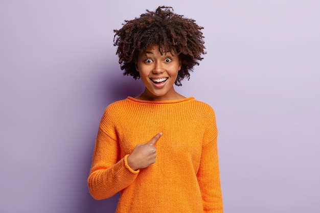 Happy dark skinned young lady points at herself, rejoices being chosen, wears orange casual jumper, smiles, isolated over purple wall. smiling optimistic woman says you mean me. Free Photo