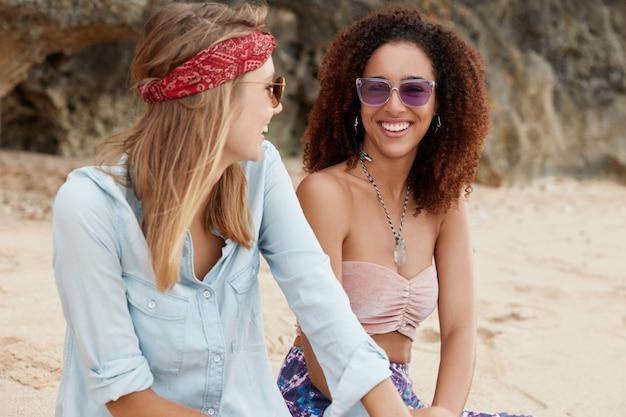 Счастливая темнокожая молодая женщина радостно смеется, глядя на свою девушку, имеет однополые отношения, наслаждается единением на пляже у океана. Бесплатные Фотографии