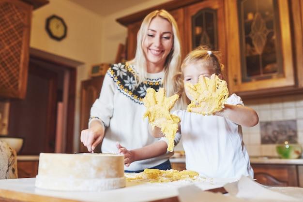 幸せな娘とママのキッチンでクッキーを焼く 無料写真