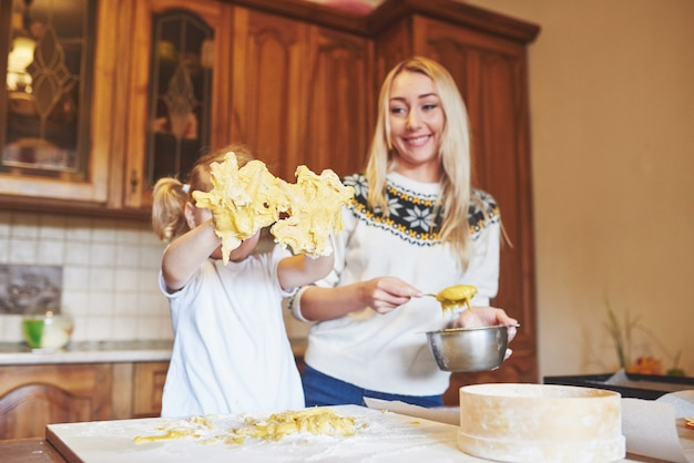 Счастливая дочь и мама на кухне пекут печенье Бесплатные Фотографии