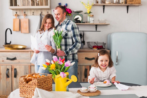 Happy daughter making cupcake near parents with greeting card Free Photo
