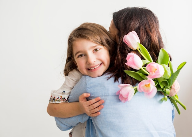 Happy daughter with tulips hugging mother Free Photo