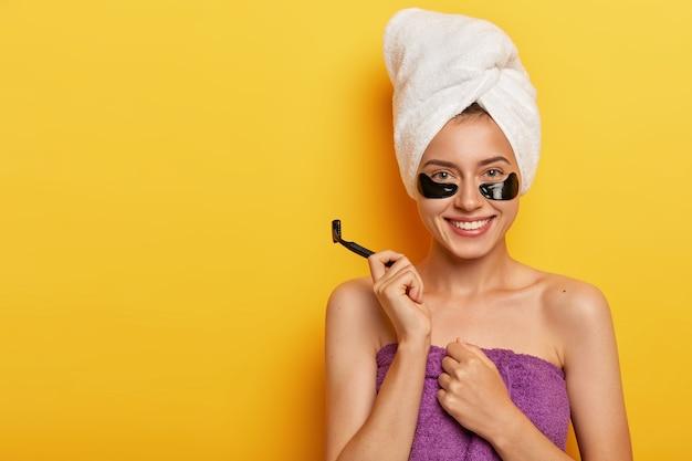 純粋な肌で幸せな喜びの女性、彼女の体を気遣い、かみそりの刃を持って、入浴とひげそりの準備をし、前向きに微笑む 無料写真