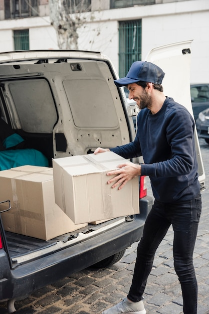 Happy delivery man carrying cardboard box near vehicle Free Photo