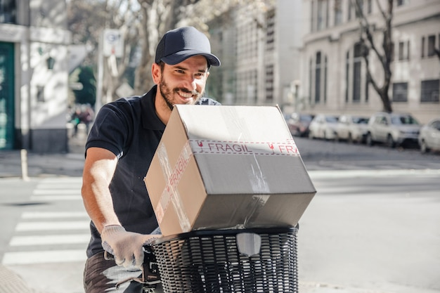 Happy delivery man delivering parcel on bicycle Free Photo