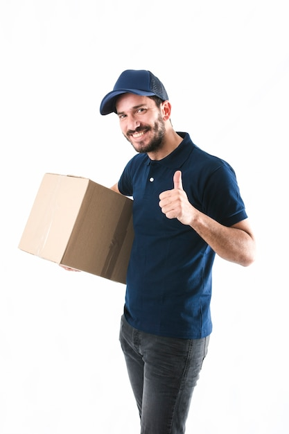 Happy delivery man holding cardboard box showing thumb up on white background Free Photo