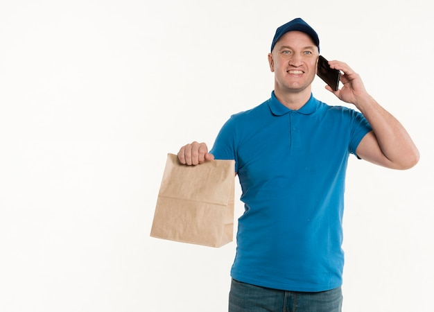 Happy delivery man holding paper bag and smartphone Free Photo