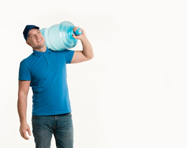 Happy delivery man holding water bottle on shoulder with copy space Free Photo