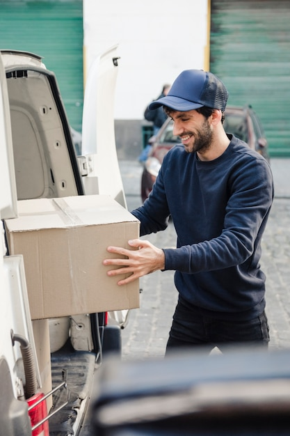 Happy delivery man unloading parcel from vehicle Free Photo