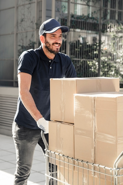 Happy delivery man with cardboard boxes walking on sidewalk Free Photo