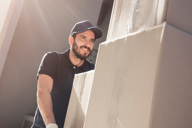 Happy delivery man with cardboard boxes Free Photo