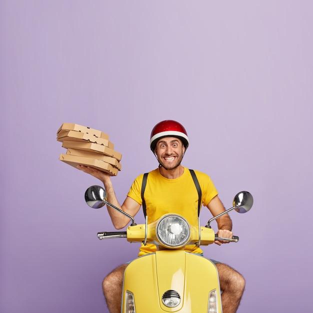 ピザの箱を持って黄色いスクーターを運転する幸せな配達員 無料写真
