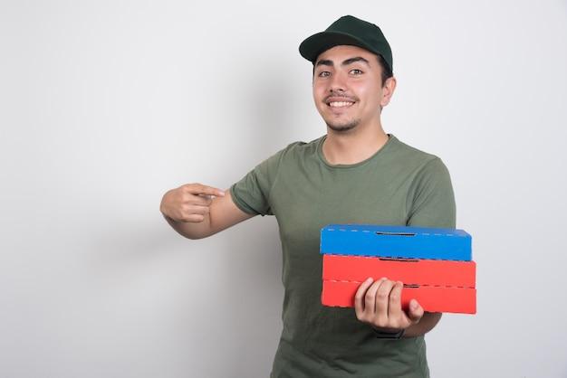 Счастливый доставщик, указывая на коробки для пиццы на белом фоне. Бесплатные Фотографии