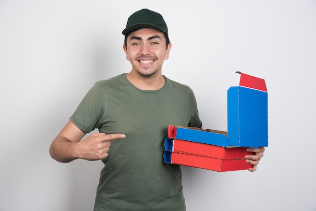 白い背景の上のピザの箱を指して幸せな配達員。 無料写真