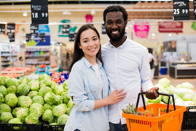Happy diverse couple in grocery store Free Photo