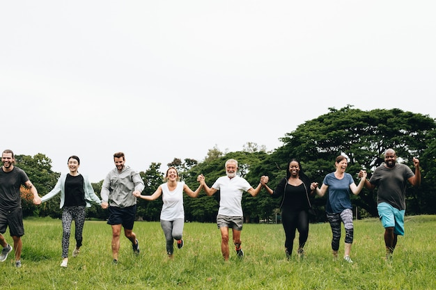 Happy diverse people holding hands in the park Premium Photo