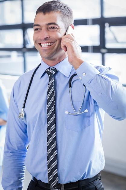 Happy doctor on the phone in the hospital Premium Photo