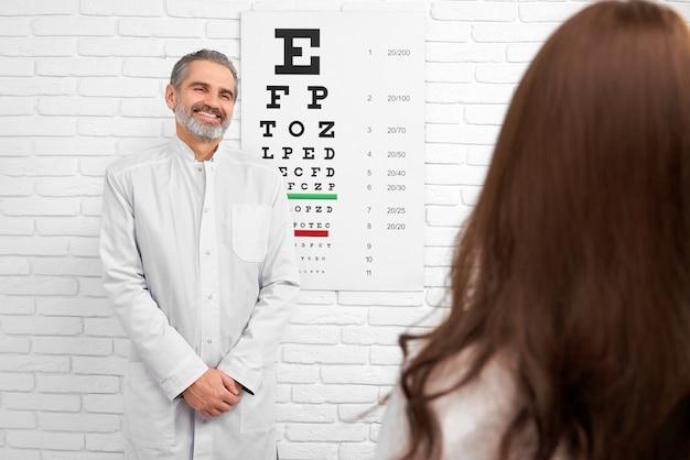 Happy doctor smiling, posing near eye chart in clinic. Premium Photo
