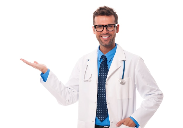 Happy doctor wearing glasses presenting something Free Photo
