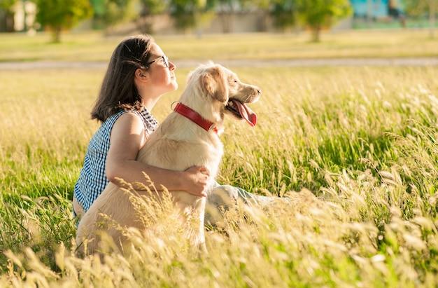 幸せな犬レトリーバーと公園で自然を楽しんでいる所有者 Premium写真