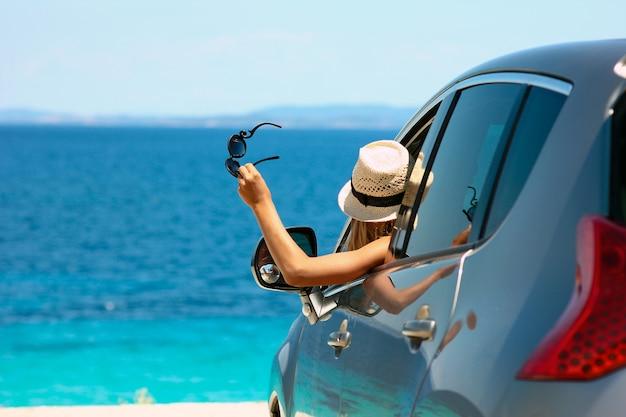 Счастливая девушка-водитель в шляпе и солнцезащитных очках в машине на море летом Premium Фотографии
