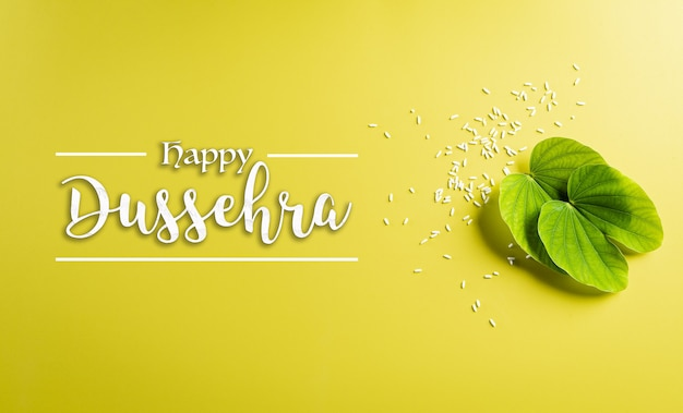 Happy dussehra concept. green leaf and rice on yellow pastel background Premium Photo