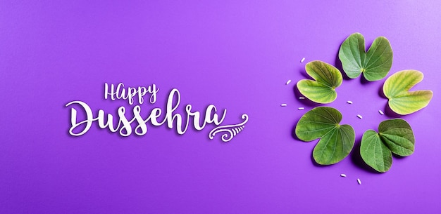 Happy dussehra with green leaves on purple surface Premium Photo