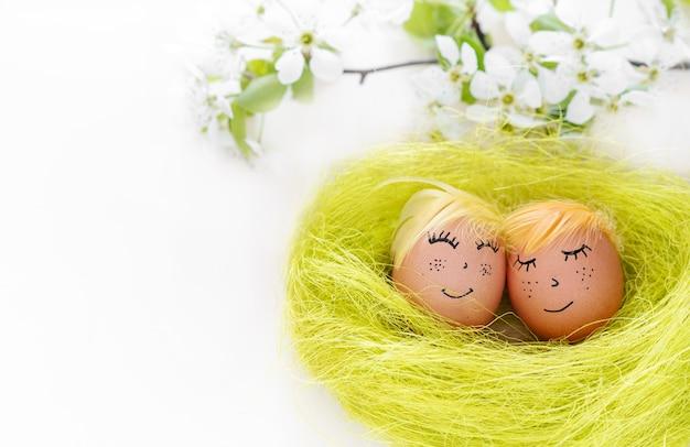 Счастливой пасхи. пара неокрашенных яиц со счастливым лицом на белом фоне с копией пространства, баннер Premium Фотографии