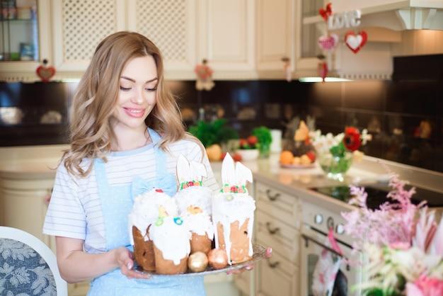 イースター、おめでとう。ケーキを持った母親がイースターの準備をします。 Premium写真