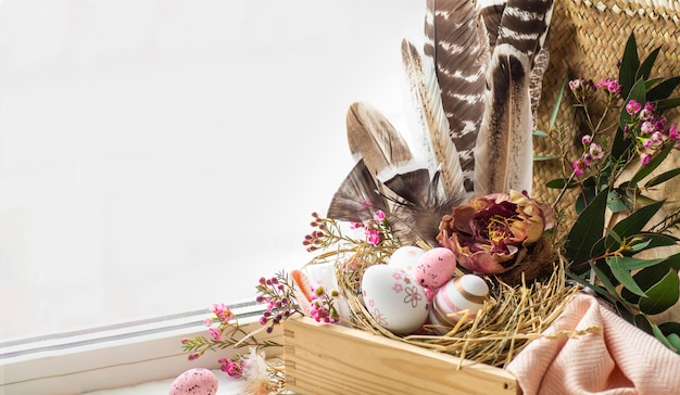 Happy easter background. pink easter eggs in a nest with floral decorations and feathers near the window Free Photo