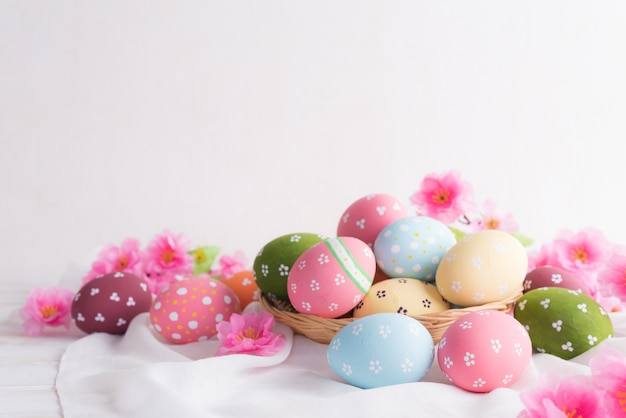 Happy easter! colorful of easter eggs in nest with flower Premium Photo
