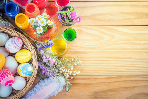 Happy easter day colorful eggs and flower a set of food coloring, acrylic paintbrush for do it yourself on brown wooden floor with copy space Premium Photo