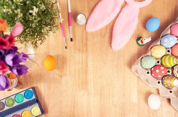 ハッピーイースター、イースターは休日の装飾のための木製の素朴なテーブルに卵を描いた。コピースペースのトップビュー。 Premium写真