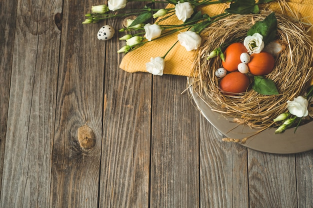 Happy easter table. easter eggs in a nest on a metal plate on a wooden table. happy easter concept Free Photo