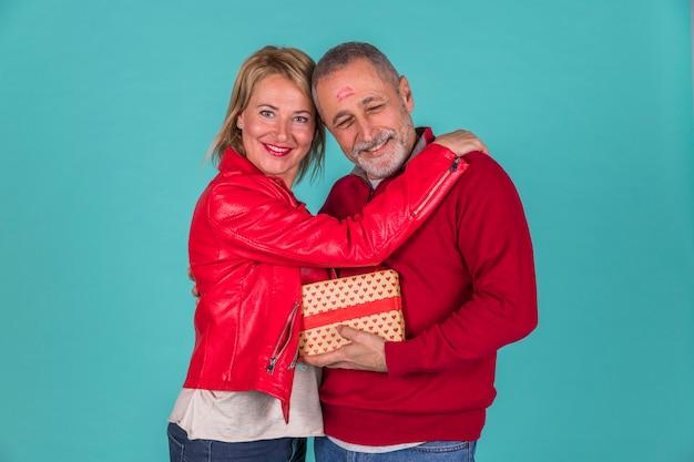 Happy elder couple hugging studio shot Free Photo