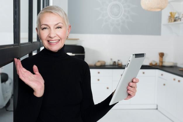 タブレットを保持している台所で幸せな老女 無料写真
