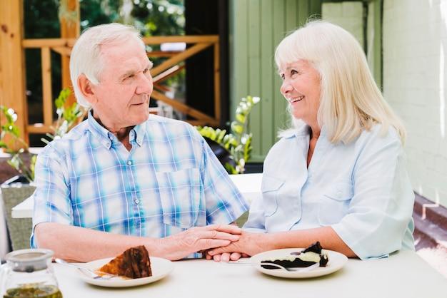 Happy elderly couple eating cake Free Photo