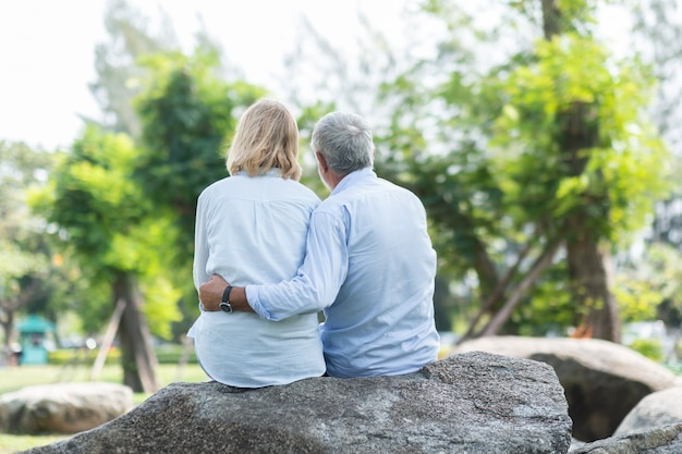 Happy elderly couple sitting with his back embracing in autumn park Premium Photo