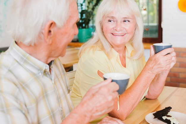 Happy elderly man and woman drinking tea Free Photo